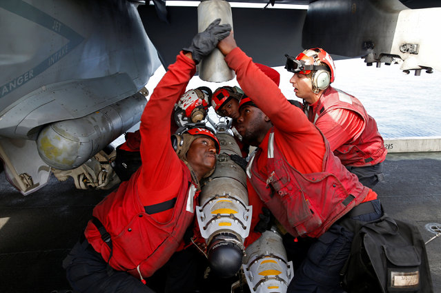US Navy sailors attach ammunition to a F/A-18 fighter jet before a mission on the flight deck of the USS Harry S. Truman aircraft carrier in the eastern Mediterranean Sea June 14, 2016. (Photo by Baz Ratner/Reuters)