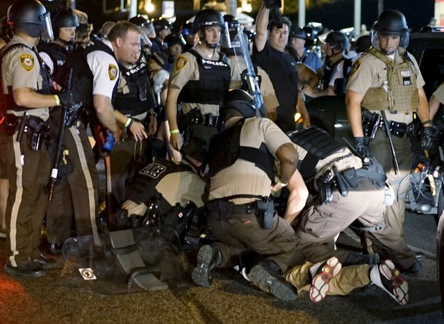 Police detain a protester in Ferguson, Missouri, August 10, 2015. (Photo by Rick Wilking/Reuters)