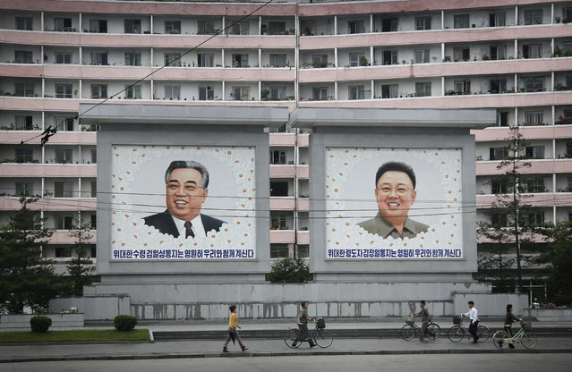 North Koreans are dwarfed against giant portraits of the late North Korean leaders Kim Il Sung and Kim Jong Il as they walk past an apartment building on Wednesday, June 22, 2016, in Wonsan, North Korea. (Photo by Wong Maye-E/AP Photo)