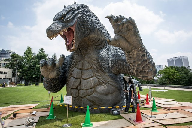 """Crewmember Tetsuo Hayashi airbrushes the final touches to a 6.6 meter replica of the famous Godzilla at Tokyo Midtown on July 15, 2014 in Tokyo, Japan. The """"MIDTOWN Meets GODZILLA"""" project is in collaboration with the Japan release of the Hollywood film version of """"Godzilla"""". The Godzilla built on the lawns of Tokyo Midtown will host a light show everynight complete with mist, audio and fire rays. (Photo by Chris McGrath/Getty Images)"""