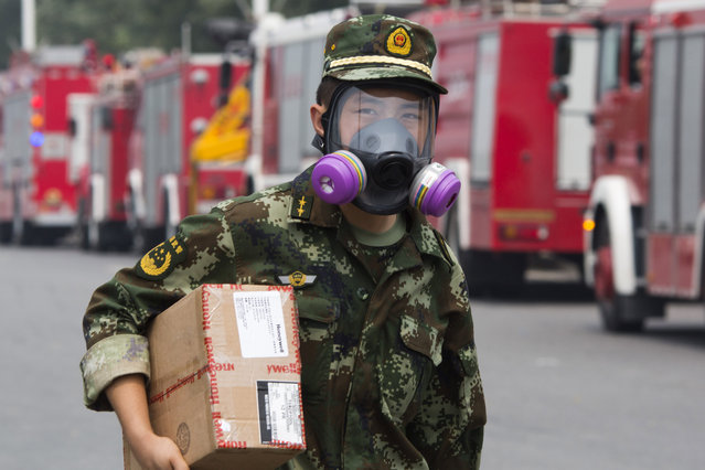 A Chinese firefighter walks near fire trucks near the site of an explosion in northeastern China's Tianjin municipality Saturday, August 15, 2015. (Photo by Ng Han Guan/AP Photo)