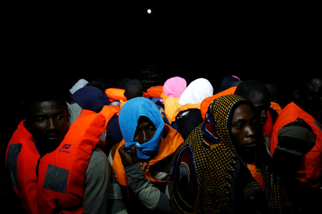 Migrants are transferred from the Migrant Offshore Aid Station (MOAS) ship Topaz Responder to an Italian Coast Guard vessel after being rescued around 20 nautical miles off the coast of Libya, June 23, 2016. (Photo by Darrin Zammit Lupi/Reuters)