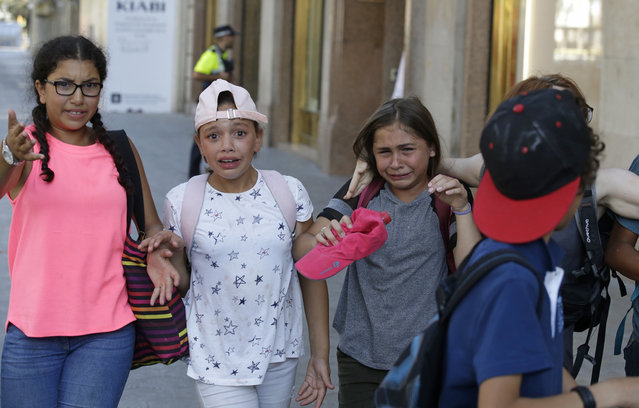 Children, some in tears, are escorted down a road in Barcelona, Spain, Thursday, August 17, 2017. Police in Barcelona say a white van has mounted a sidewalk, struck several people in the city's Las Ramblas district. (Photo by Manu Fernandez/AP Photo)