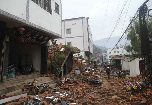 Debris of collapsed houses are seen scattered along a street, after a deadly earthquake hit Longtoushan town on Sunday, in Ludian county, Zhaotong, Yunnan province August 4, 2014. (Photo by Reuters/China Daily)