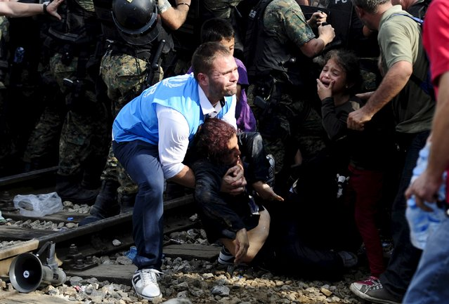 A woman collapses at the border line dividing Macedonia and Greece August 21, 2015. At least 1,000 migrants and refugees pressed against Macedonian police lines on the Greek-Macedonian border on Friday and at least 10 people appeared to faint in the crush. People could be heard screaming and medical workers raced to treat those who passed out or were hurt. (Photo by Ognen Teofilovski/Reuters)