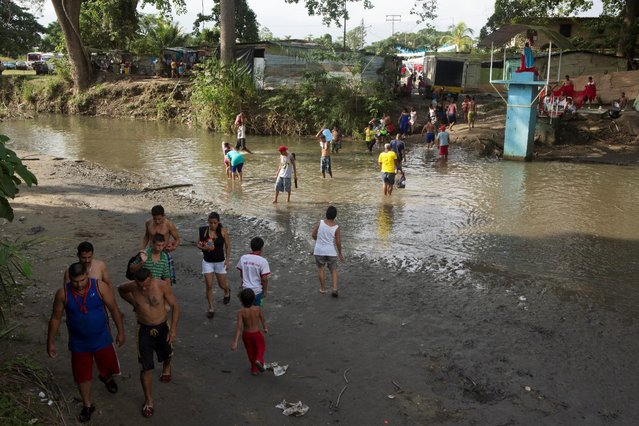 People cross a river at a hamlet in the Sorte Mountain on the outskirts of Chivacoa, in the state of Yaracuy, Venezuela October 11, 2015. (Photo by Marco Bello/Reuters)