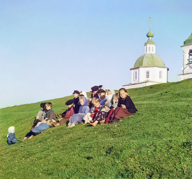 Photos by Sergey Prokudin-Gorsky. Russian children sitting on the side of a hill near a church and bell tower in the countryside near White Lake, in the north of European Russia. The picture was taken at the church in the background Pyatnitskaya Belozersk (not preserved). Novgorod Province, White Lake County, 1909