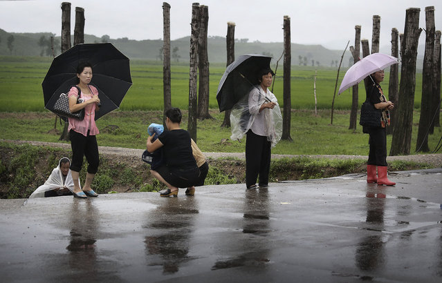 North Koreans shelter themselves from the rain as they wait for transportation along the road, Saturday, July 26, 2014 in the North Pyongan Province, North Korea. (Photo by Wong Maye-E/AP Photo)