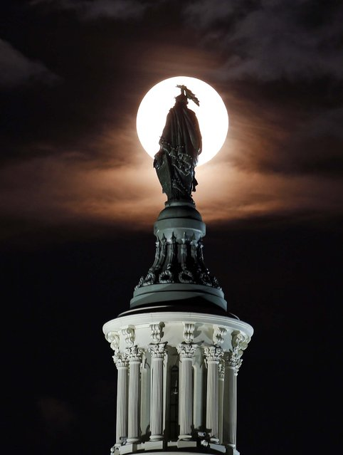 The Supermoon is seen as it rises through the clouds behind the bronze Statue of Freedom by Thomas Crawford atop the U.S. Capitol in Washington. (Photo by Alex Brandon/Associated Press)