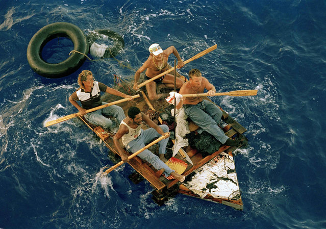 Cuban refugees row a makeshift raft in the Florida straits, August 25, 1994. The refugees were picked up by the U.S. Coast Guard cutter Gallatin and were then transferred to a Navy ship which would transport them to a refugee camp at the U.S. Naval Base in Guantanamo Bay, Cuba. (Photo by Steve Helber/AP Photo)