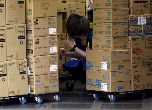 A shop clerk works between cardboard boxes outside a discount drug store at a shopping district in Tokyo, Japan, July 29, 2015. Japanese retail sales rose 0.9 percent in the year to June but the pace of growth slowed for a second straight month, a sign consumer spending has yet to build enough momentum to be a key driver of economic growth. (Photo by Yuya Shino/Reuters)