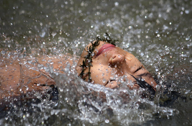 An Indian youth swims in the Dhansari river as she cools off during a hot summer day in Dimapur, India's northeastern state of Nagaland, on May 19, 2012. (Photo by STR/AFP)