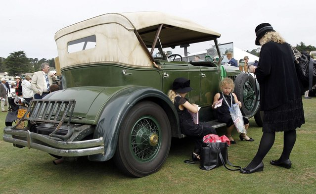 Sisters Minerva (L) and Octavia Miller sit on the running board of a 1928 Chrysler Imperial Traveler LeBaron Phaeton during the Concours d'Elegance at the Pebble Beach Golf Links in Pebble Beach, California, August 17, 2014. (Photo by Michael Fiala/Reuters)