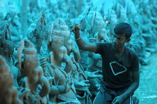 An Indian artisan works on biodegradable idols of Hindu god Lord Ganesh, made of mud and bamboo, at a blue tarp-covered workshop on the outskirts of Hyderabad on August 21, 2014. Some 2,500 idols are being made by the artisans for the upcoming Hindu Ganesh festival, where the idols will be immersed in water bodies as part of religious rituals. (Photo by Noah Seelam/AFP Photo)