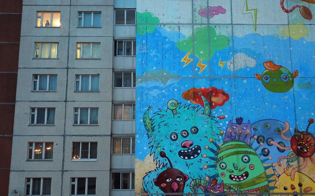 A mural depicting an artist's impression of viruses is seen outside a block of flats in Gatchina, Leningrad Region, some 20 km south of St Petersburg, Russia on March 31, 2020, during the pandemic of the novel coronavirus (COVID-19). As of 31 March 2020, Russia has reported more than 2300 confirmed cases of the novel coronavirus, with 14 confirmed cases in Leningrad Region. (Photo by Peter Kovalev/TASS)