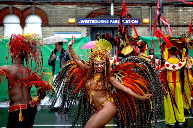 Performers dance through the rain during the Notting Hill Carnival by on August 25th, 2014 in London, England.   (Photo by Mary Turner/Getty Images)
