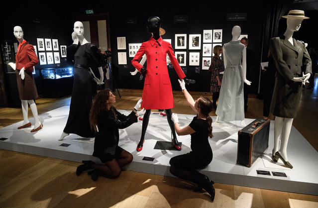 Two gallery assistants pose with Valentino Couture red dress coat (reserve £1000-1500) during a preview of items from the sale of actrees Audrey Hepburn's personal collection at Christies on September 22, 2017 in London, England. The sale sees over 500 lots from the actresses career and personal life being sold at auction. (Photo by Leon Neal/Getty Images)