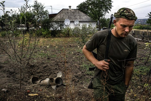 A member of the Donetsk People's Republic walks by an unexploded rocket that fell in the backyard of a villager in Troitsko-Khartsyzk, about 26 miles from Donetsk, Ukraine, on August 28, 2014. Declaring that Russian troops had crossed into Ukraine, President Petro Poroshenko canceled a planned visit to Turkey and convened a meeting of the national security council to focus on the 'marked aggravation of the situation' in the southeast of his country. (Photo by Mauricio Lima/The New York Times)