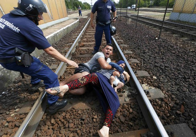 Hungarian policemen stand by the family of migrants protesting on the tracks at the railway station in the town of Bicske, Hungary, September 3, 2015. (Photo by Laszlo Balogh/Reuters)