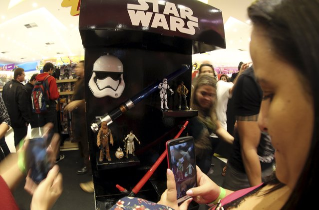 """Customers take photograpks of the new toys from the upcoming film """"Star Wars: The Force Awakens"""" on """"Force Friday"""" in Sao Paulo, Brazil, September 4, 2015. (Photo by Paulo Whitaker/Reuters)"""