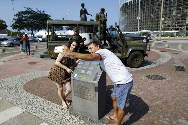 2016 Rio Olympics, Olympic Park on July 29, 2016. People pose for a selfie with soldiers on Copacabana. (Photo by Ivan Alvarado/Reuters)