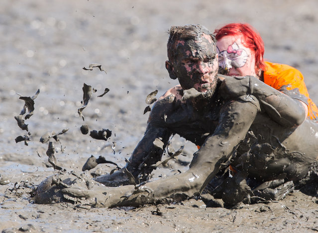 In this July 30, 2016 picture participants challenge for the ball during the Mud Olympics event at the North Sea tideland in Brunsbuettel, Germany. Since 2004, teams of different disciplines, such as mud soccer, mud handball and mud sledding, compete against each other. (Photo by Daniel Bockwoldt/DPA via AP Photo)
