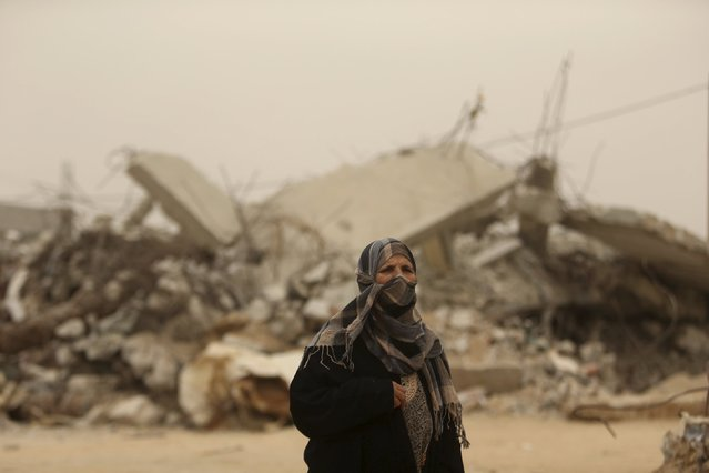 A Palestinian woman looks on as she stands in front of the ruins of a house, that witnesses said was destroyed by Israeli shelling during a 50-day war in 2014 summer, during a sandstorm in Khan Younis in the southern Gaza Strip September 8, 2015. (Photo by Ibraheem Abu Mustafa/Reuters)