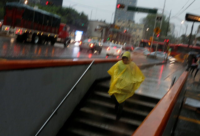 A woman wearing a raincoat enters a metro station during heavy rain in Mexico City, Mexico, August 2, 2016. (Photo by Tomas Bravo/Reuters)