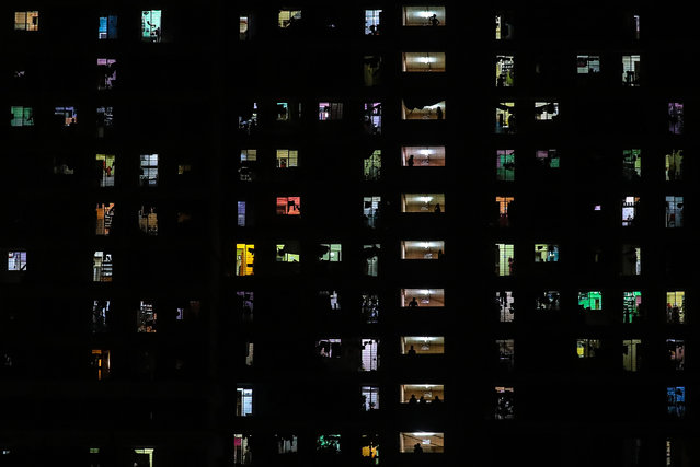 People are seen in their windows and balconies of a residential building in Mumbai, India, 27 April 2020. India's initial 21-day lockdown is extended until 03 May 2020 in an attempt to curb the spread of of the SARS-CoV-2 coronavirus which causes the COVID-19 disease. (Photo by Divyakant Solanki/EPA/EFE)