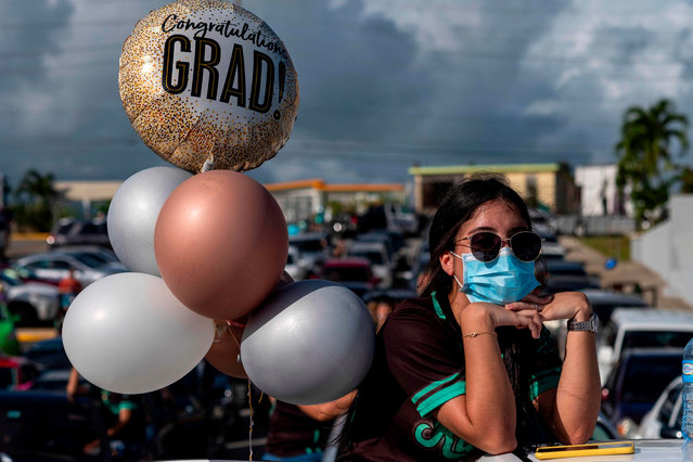 A graduating student from the Ramon Power Y Giralt High School wears a facemask during a symbolic graduation from their cars to maintain social distance at a parking lot in Las Piedras, Puerto Rico, on May 13, 2020. The event was organized by the municipal government to congratulate the local graduates whose traditional ceremonies were canceled due to the coronavirus pandemic, with the condition of staying inside their vehicles. (Photo by Ricardo Arduengo/AFP Photo)