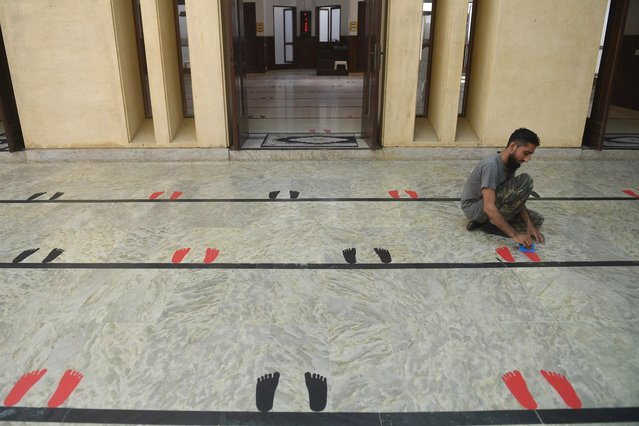 A Muslim devotee places stickers of feet silhouettes on the floor of a Mosque to maintain social ahead of the Muslim holy month of Ramadan during a government-imposed nationwide lockdown as a preventive measure against the COVID-19 coronavirus, in Karachi on April 23, 2020. (Photo by Asif Hassan/AFP Photo)