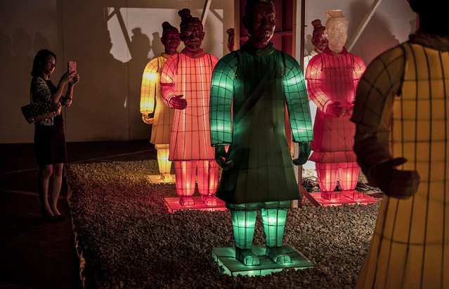 A Chinese woman takes pictures of lit statues replicating China's famous Terracotta Warriors at an exhibtion on September 3, 2014 in Beijing, China. (Photo by Kevin Frayer/Getty Images)