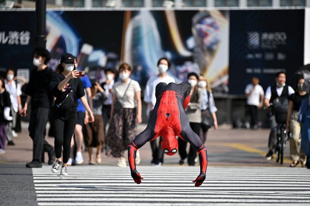 A man wearing a Spiderman costume jumps across Shibuya crossing in Tokyo on June 8, 2020. (Photo by Charly Triballeau/AFP Photo)