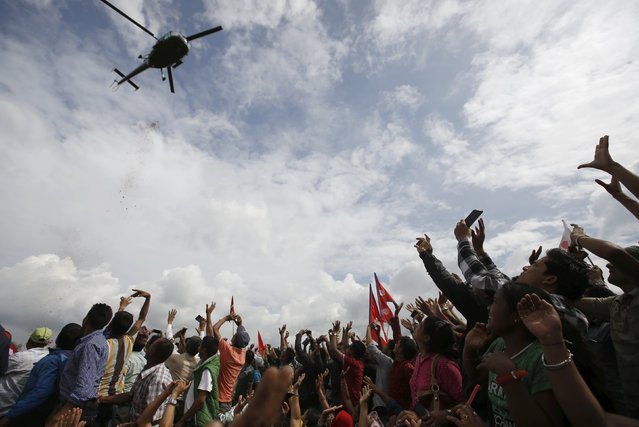 People cheer towards a passing helicopter as they gather during a celebration a day after the first democratic constitution was announced in Kathmandu, Nepal September 21, 2015. (Photo by Navesh Chitrakar/Reuters)