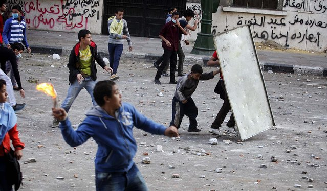 Protesters throw rocks and Molotov cocktails at police in downtown Cairo, November 25, 2012. On Sunday, the Egyptian justice minister joined criticism of a sweeping edict issued Thursday by President Mohamed Morsi that exempted the president's decrees from judicial review until ratification of a constitution. (Photo by Tara Todras-Whitehill/The New York Times)