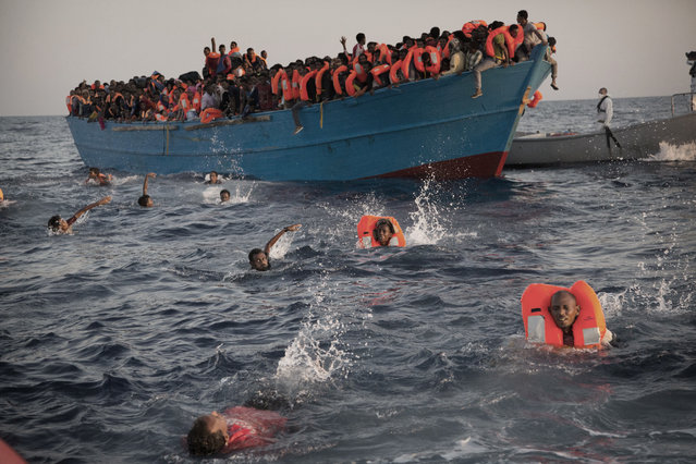 Migrants, most of them from Eritrea, jump into the water from a crowded wooden boat as they are helped by members of an NGO during a rescue operation at the Mediterranean sea, about 13 miles north of Sabratha, Libya, Monday, August 29, 2016. Thousands of migrants and refugees were rescued Monday morning from more than 20 boats by members of Proactiva Open Arms NGO before transferring them to the Italian cost guards and others NGO vessels operating at the zone. (Photo by Emilio Morenatti/AP Photo)
