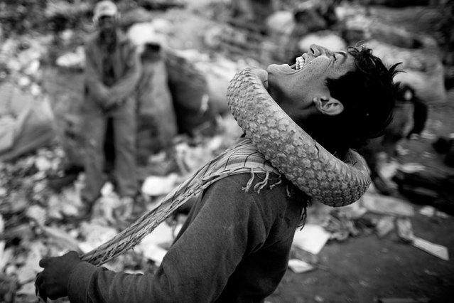 An Afghan man wears a tire around his neck while sorting through plastic and metal items near a rubbish dump on October 27, 2010 on the southern outskirts of Kabul, Afghanistan. According to the Global Anti-Incinerator Alliance (GAIA), about 15 million people throughout the developing world earn a living from collecting garbage. (Photo by Majid Saeedi/Getty Images)