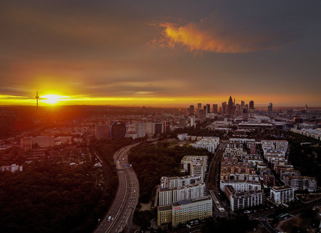 The sun rises over Frankfurt, Germany, with the buildings of the banking district at right, early Thursday, July 2, 2020. (Photo by Michael Probst/AP Photo)