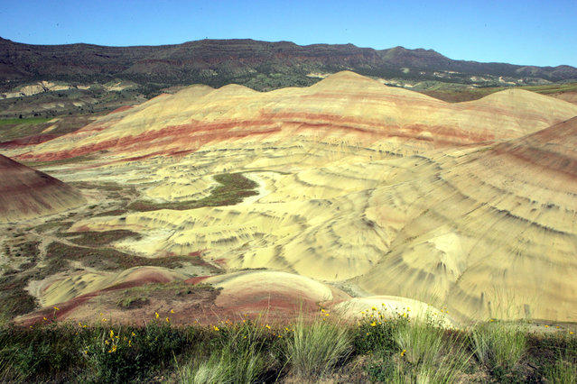 In this May 26, 2005, file photo, a half mile hike offers one of many spectacular views at the Painted Hills Unit of the John Day Fossil Beds National Monument near Mitchell, Ore. Trip visits to the national monument, along with other Oregon areas such as Crater Lake National Park and Smith Rock State Park, surged in 2014 as part of a $2.3 million Seven Wonders campaign by Wieden+Kennedy ad agency. (Photo by Don Ryan/AP Photo)