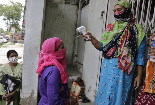 An Indian woman's temperature is checked by another before she enters a bank in Ahmedabad, India, Monday, July 20, 2020. The country of 1.4 billion people, has the third most number of coronavirus cases in the world. (Photo by Ajit Solanki/AP Photo)