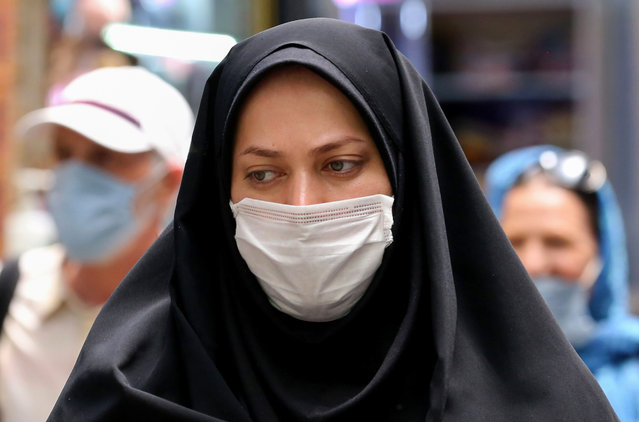 An Iranian women wearing a protective mask amid the COVID-19 pandemic, shops at the Tajrish Bazaar market in the capital Tehran on July 14, 2020. (Photo by Atta Kenare/AFP Photo)
