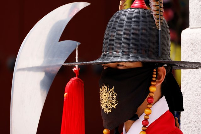 A worker wearing traditional dress wears a mask to prevent the spread of the coronavirus disease (COVID-19) during the daily re-enactment of the changing of the Royal Guards at Gyeongbok Palace in central Seoul, South Korea, July 30, 2020. (Photo by Kim Hong-Ji/Reuters)
