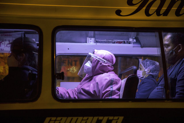 Commuters using protective gear amid the coronavirus pandemic sit inside a public bus in Lima, Peru, Thursday, August 13, 2020. (Photo by Rodrigo Abd/AP Photo)
