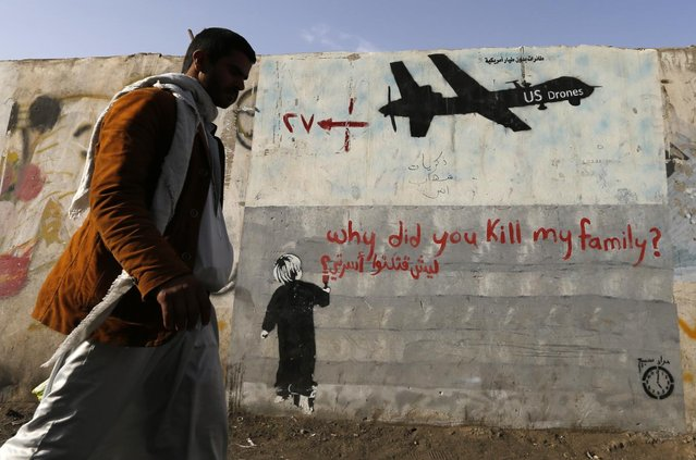 A man walks past a graffiti, denouncing strikes by U.S. drones in Yemen, painted on a wall in Sanaa November 13, 2014. (Photo by Khaled Abdullah/Reuters)