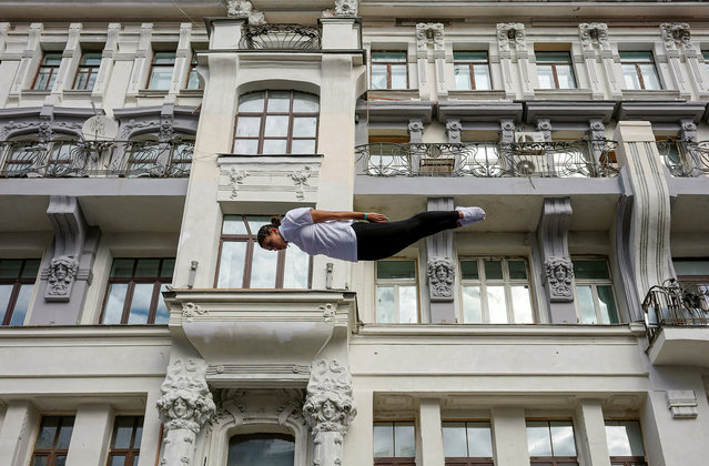 A gymnast performs on a street during the celebrations for the City Day in Moscow, Russia September 10, 2016. (Photo by Maxim Zmeyev/Reuters)