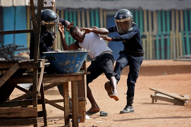 Policemen detain a demonstrator during a protest against president Alassane Ouattara's decision to stand for a third term, in Abidjan, Ivory Coast, August 13, 2020. (Photo by Luc Gnago/Reuters)
