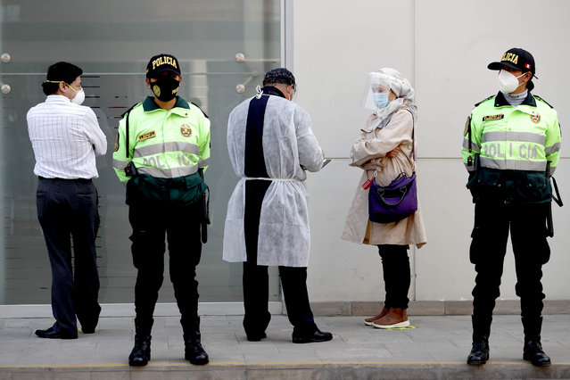 A person from the health service receives a woman at the entrance of the Center for Clinical Studies of the Cayetano Heredia University while they are guarded by members of the police, in Lima, Peru, 09 September 2020. The Chinese laboratory Sinopharm began on 09 September in Peru the initial clinical trials of its vaccine against COVID-19. The laboratory reported that it performs these same tests in Argentina, Morocco and Saudi Arabia. (Photo by Paolo Aguilar/EPA/EFE/Rex Features/Shutterstock)
