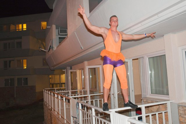 """A student at Bangor University balances on a balcony dressed for the """"tight and bright"""" night out on March 29 2012. He is one of around a 1000 British university students staying at the Hotel Delfin at the Zelena Laguna resort on the inaugural ILOVETOUR to the town of Porec in Croatia. The tour organizes various sports and themed events and club nights. (Photo by Peter Dench/Getty Images Reportage)"""