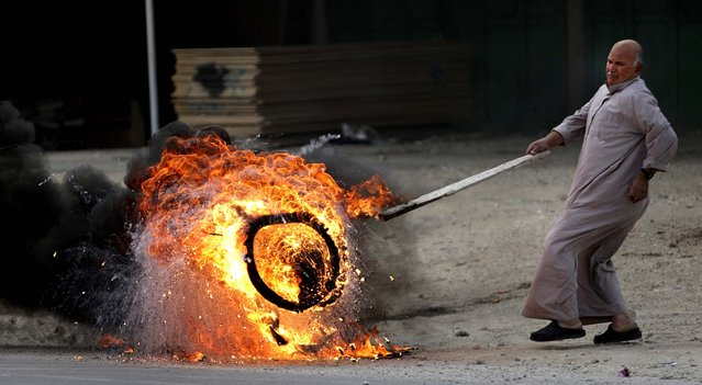 A man pushes a burning tire in the West Bank town of Nablus during a rally in support of Palestinian prisoners, February 22, 2013. (Photo by Nasser Ishtayeh/Asociated Press)