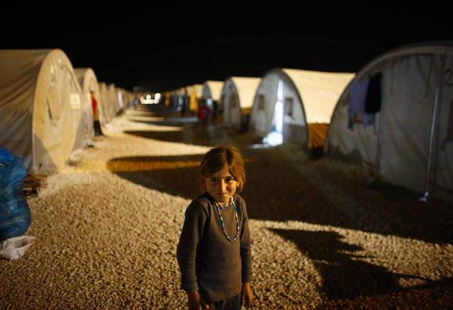 A Kurdish refugee girl from the Syrian town of Kobani stands in a refugee camp in the border town of Suruc, Sanliurfa province November 19, 2014. (Photo by Osman Orsal/Reuters)